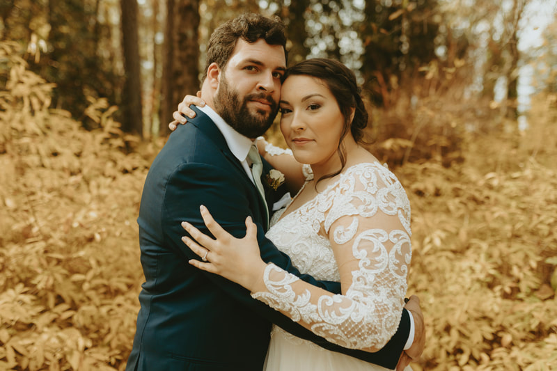 bride in lace dress with groom in charcoal suit with arms around each other and fall greenery behind them