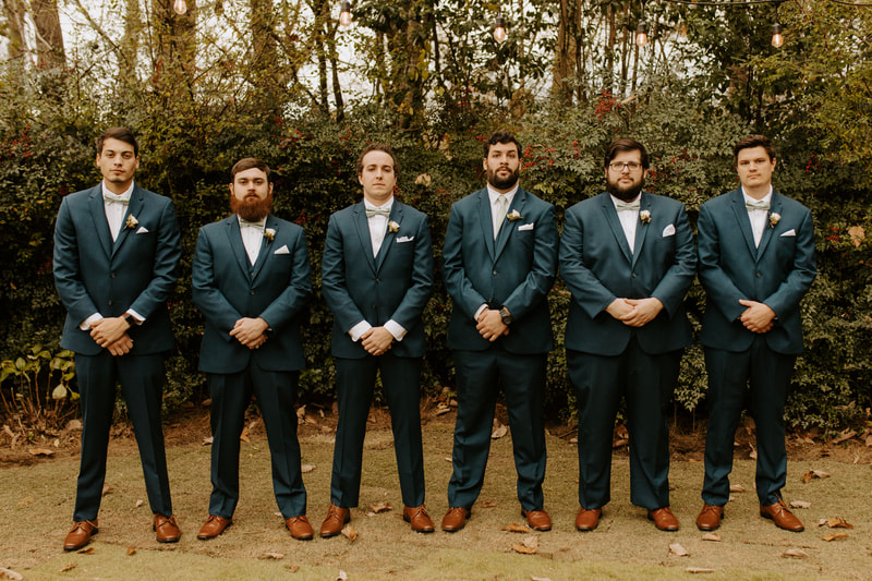 groom with groomsmen in matching charcoal suits standing in Four Oaks' gardens