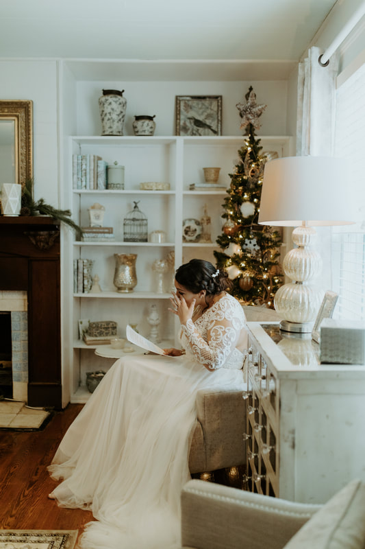 bride wiping away tear while reading letter from groom and sitting in Christmas decorated farmhouse bridal suite
