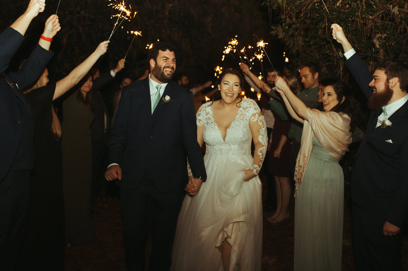 bride and groom laughing during sparkler grand exit