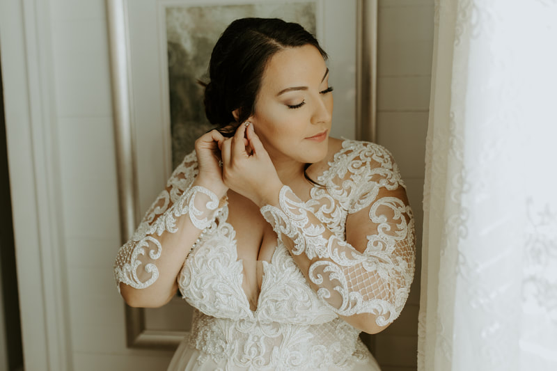 bride in lace dress with deep v-neck putting in earrings by farmhouse window
