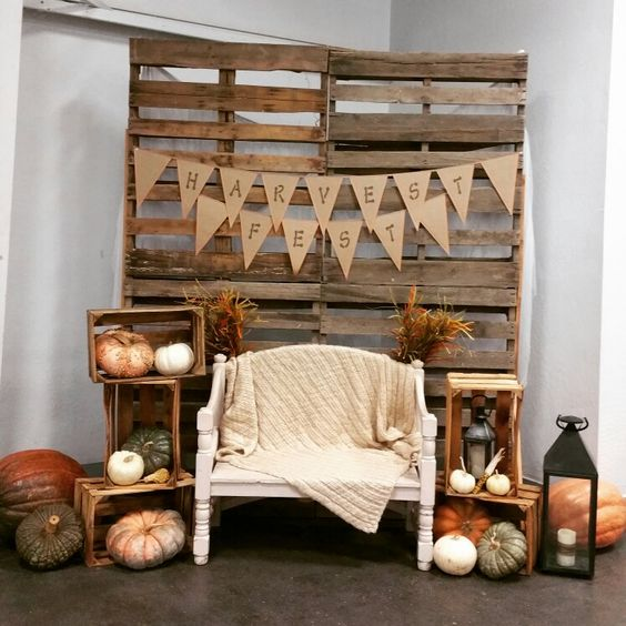 fall photo booth with white bench, wood backdrop and pumpkins