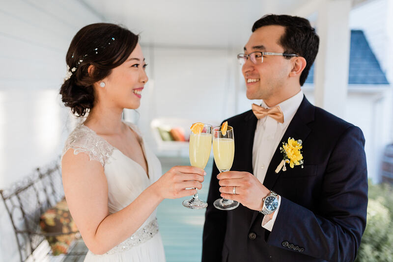asian newlyweds toasting with mimosas on farmhouse front porch
