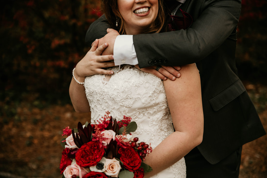 groom hugging bride from behind at fall moody wedding