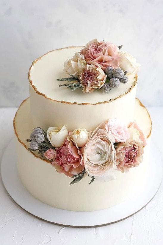 simple wedding cake with white frosting and soft pastel florals