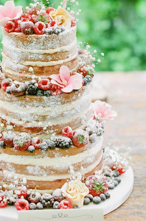 naked wedding cake with frosted flowers, mixed berries, powdered sugar, and baby's breath