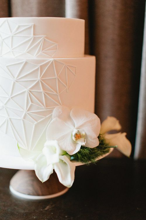 all-white wedding cake with geometric piping