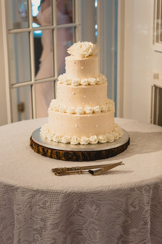 classic wedding cake with rose icing and pearl decorations