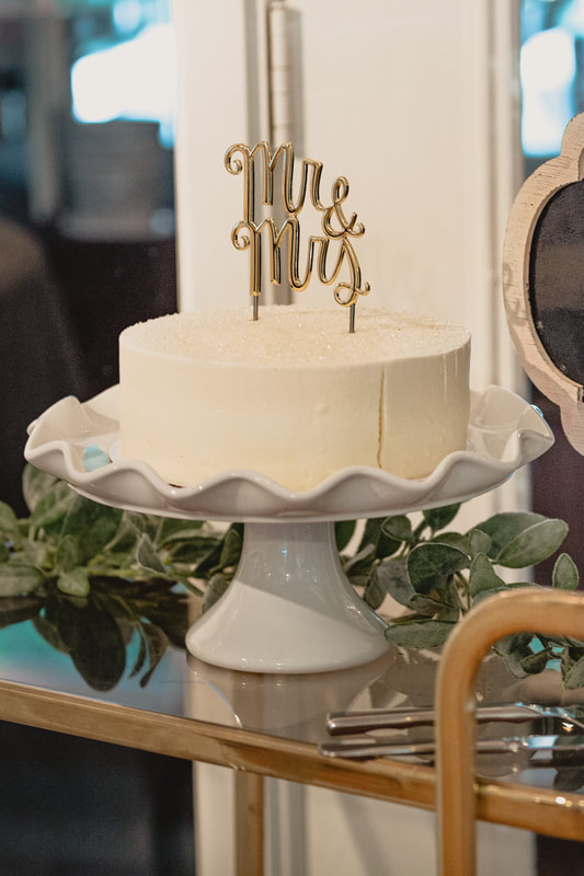 simple vegan wedding cake with gold cake topper and crystal sugar on top