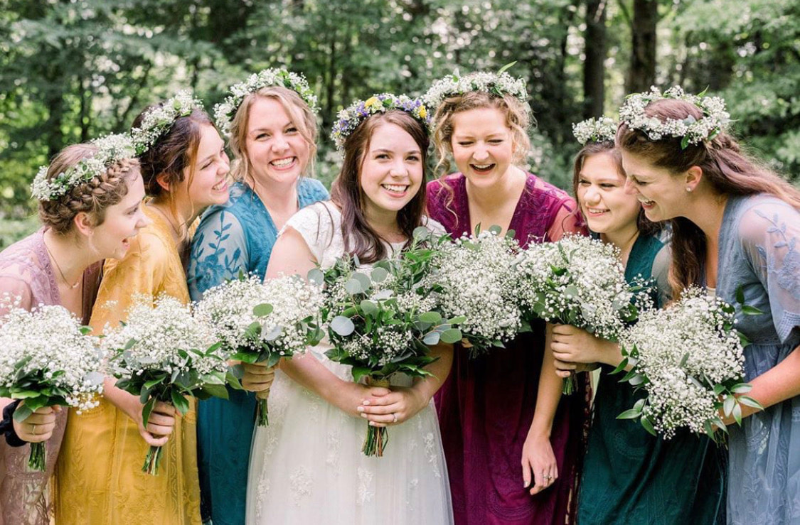 Bride and bridesmaid with braids and wispy flower crowns made of baby's breath and greenery.