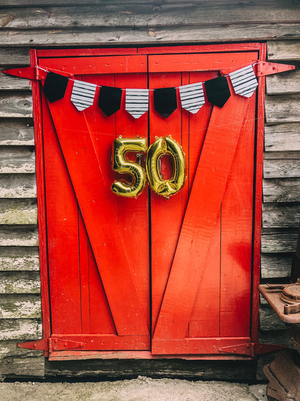 50th anniversary decorations on red barn door