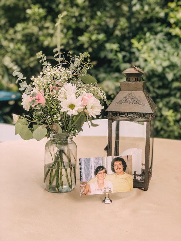 couple photos with flower arrangements and lantern centerpiece
