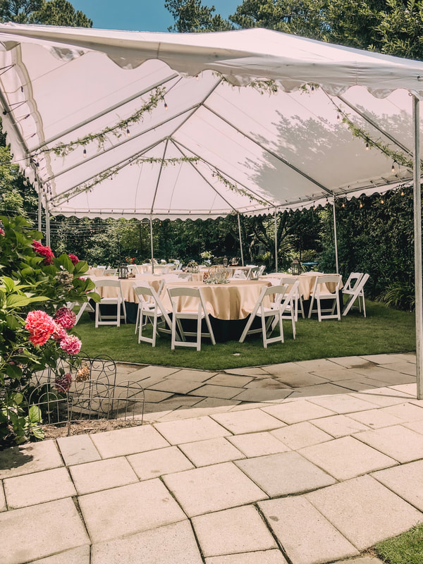 outdoor tent with greenery and table setup