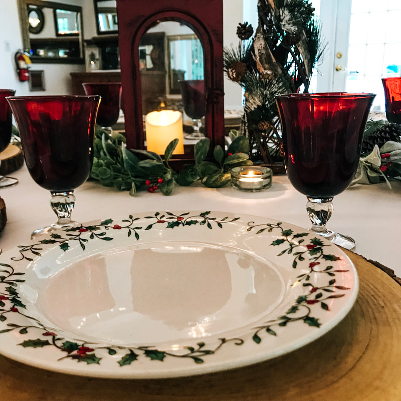 holly rimmed china on wood slice place setting