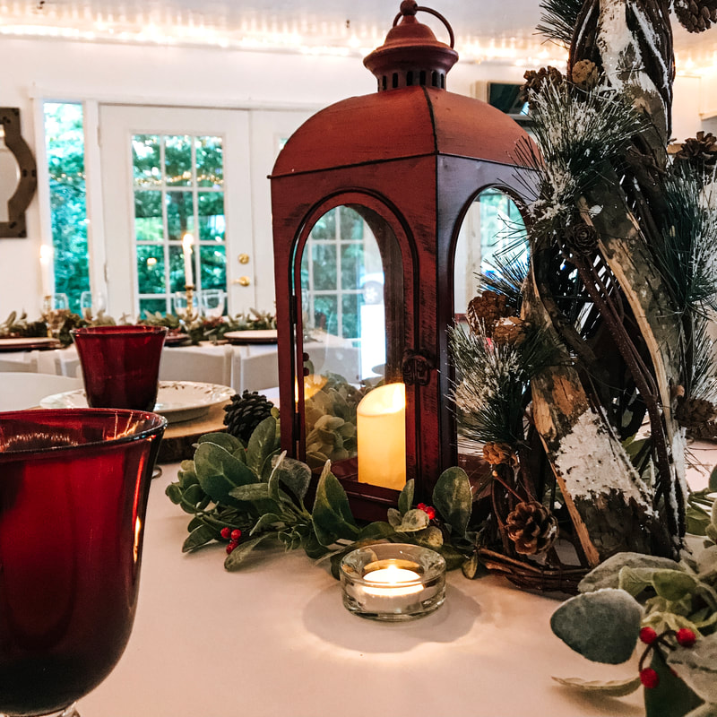 holiday party centerpiece with lantern, frosted pine, candles and holly