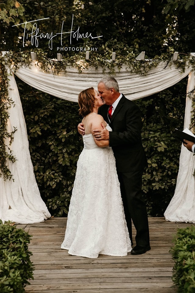 "middle-aged couple kiss at wedding after ""i Do"""