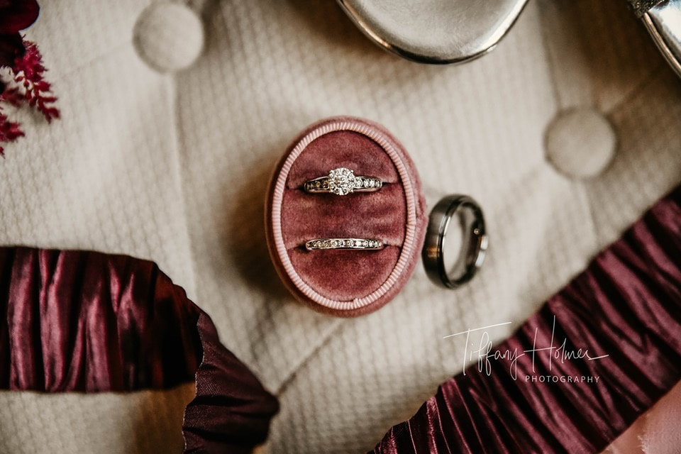 engagement ring and wedding band in velvet ring box next to groom's silver wedding band