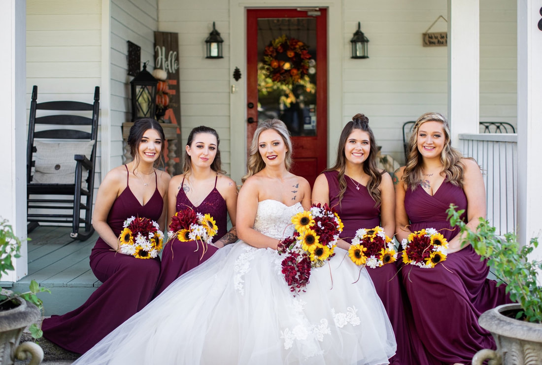 bride on farmhouse front porch with bridesmaids in burgundy all holding bouquets with sunflowers
