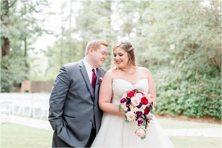 newlyweds at romantic wedding with colors of blush, red, and wine