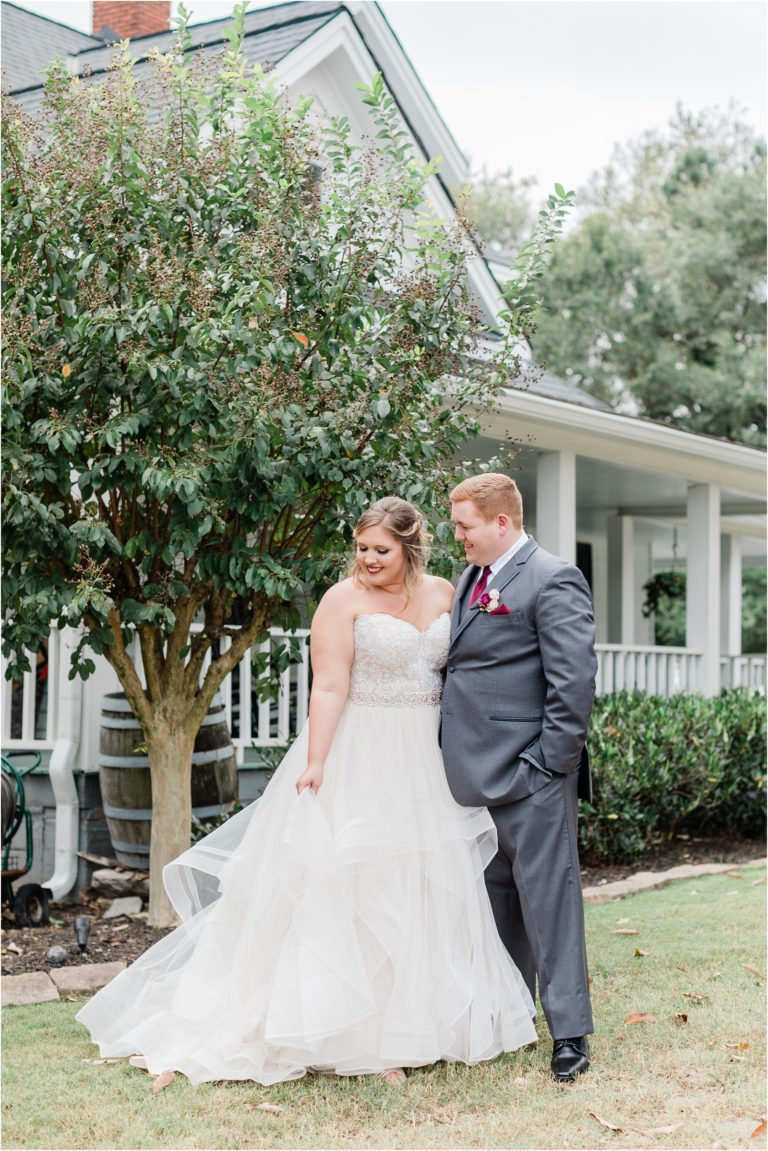 groom and bride posing in front of Four Oaks Manor by tree