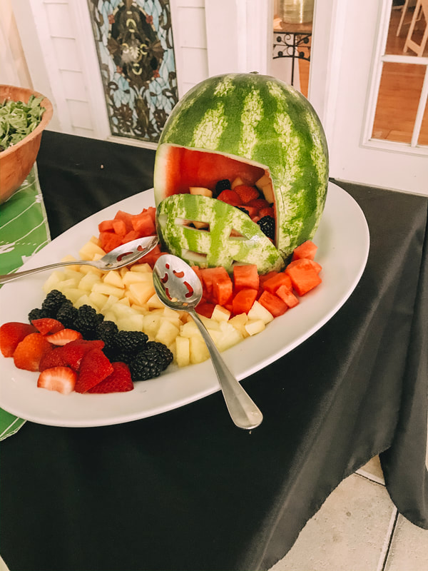 assorted fruit coming out of watermelon shaped like a football helmet