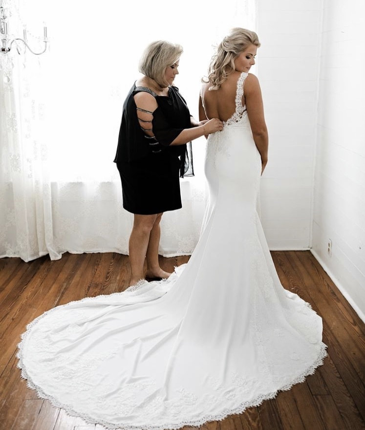 mother of the bride buttoning daughter's wedding dress