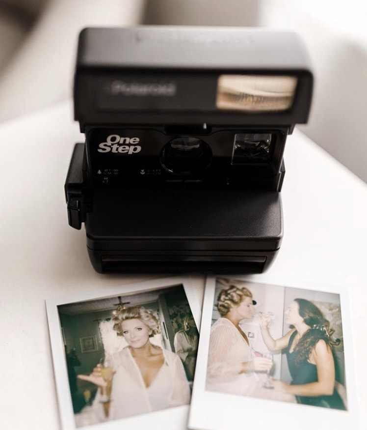 black Polaroid camera with photos of bride getting ready