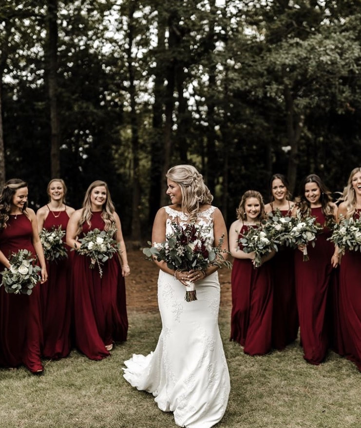 bride with extravagant bouquet posing with bridesmaids in wine colored dresses
