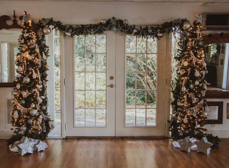 Christmas decorated farmhouse doors with greenery and Christmas trees