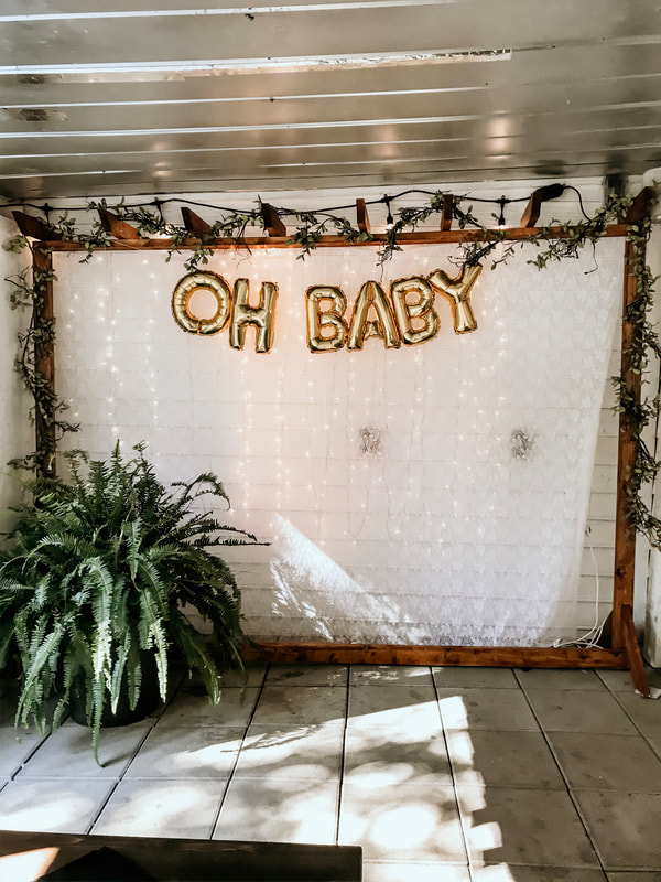 oh baby photo booth with balloons, greenery and lights