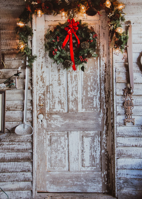 smokehouse door decorated with Christmas wreath