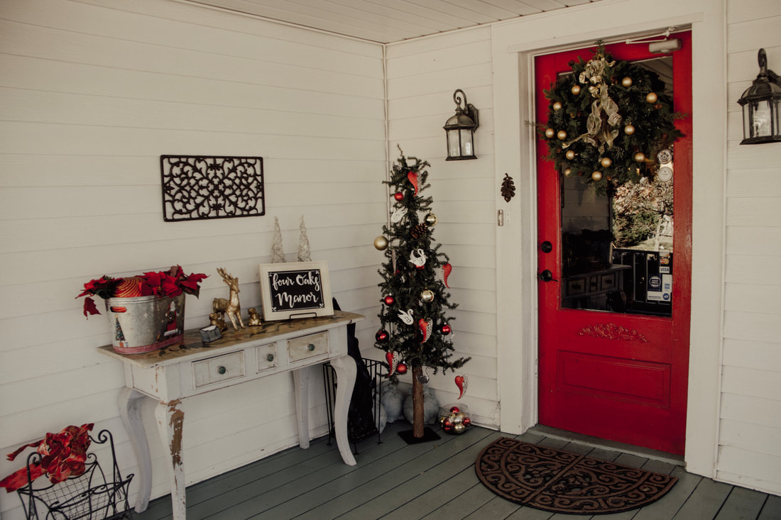 Four Oaks Manor's farmhouse front door decorated for Christmas