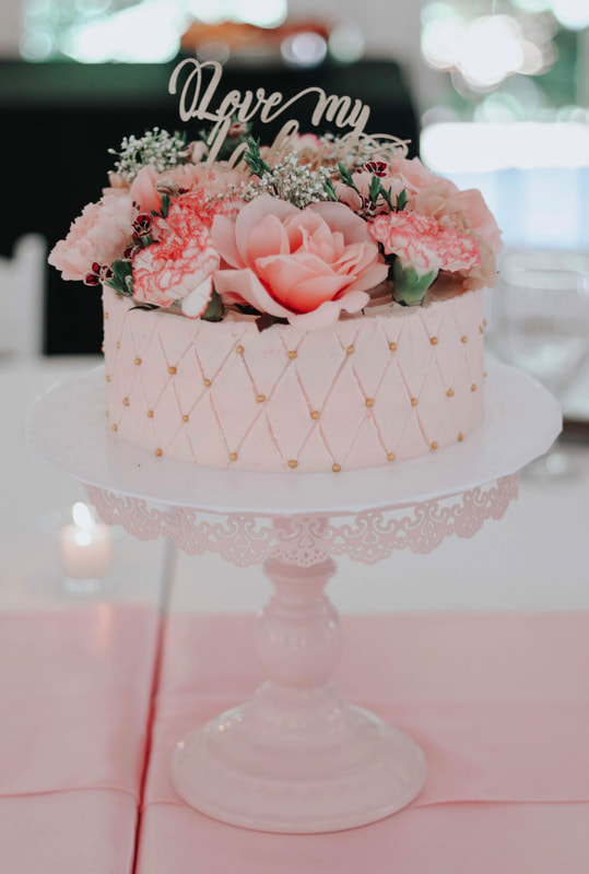Pink bridal party cake with pink flowers on light pink cake stand