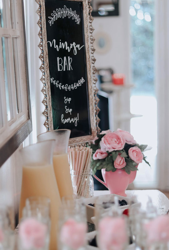 Mimosa bar set up for bridal shower with pink flowers