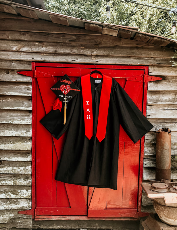 graduation cap and gown by red farm door