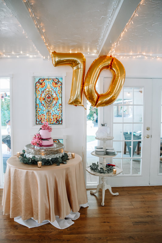 70th birthday cake table and giant gold balloons