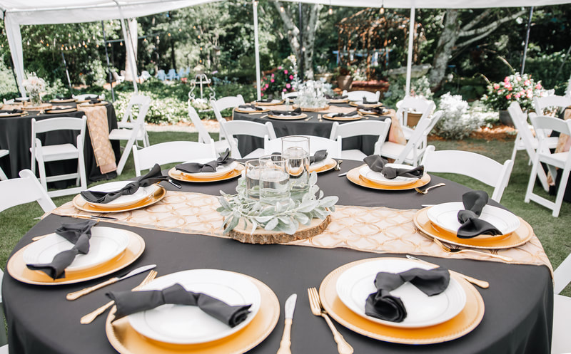 black and gold table decor under tent