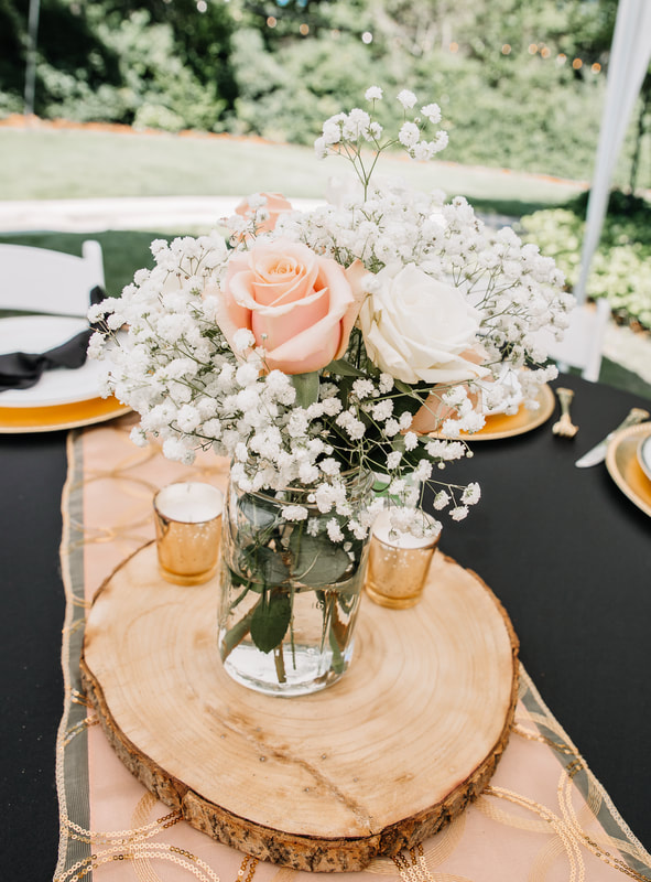 Peach and white flower centerpiece on wood slice