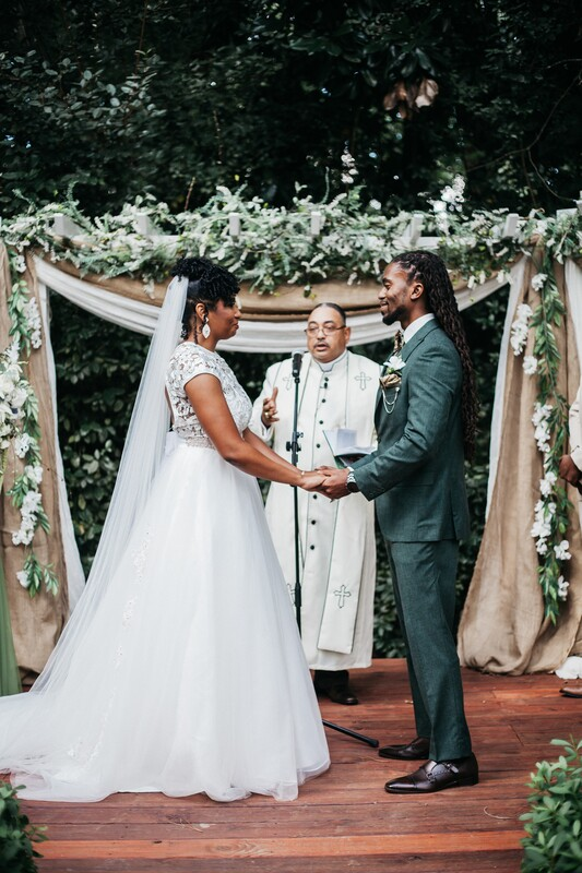 black couple at altar decorated with burlap and faux greenery