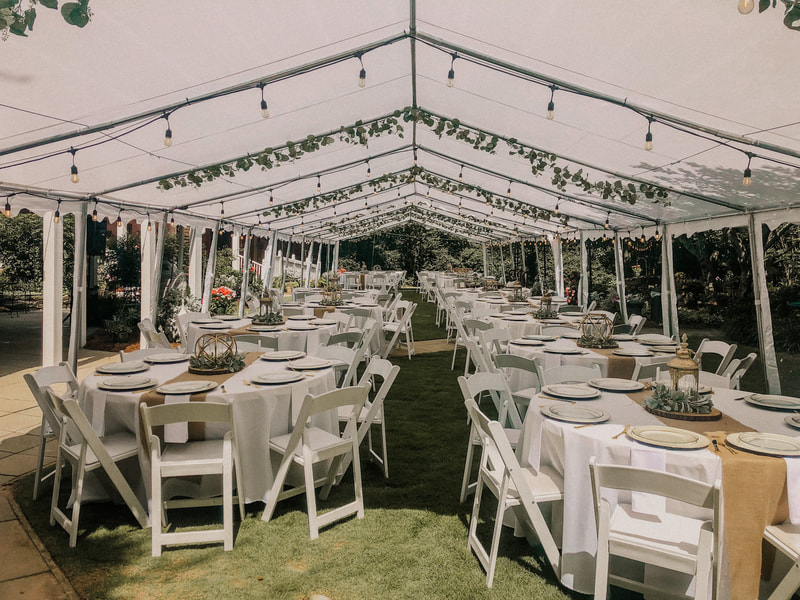 summer outdoor wedding reception under tents with lights and greenery