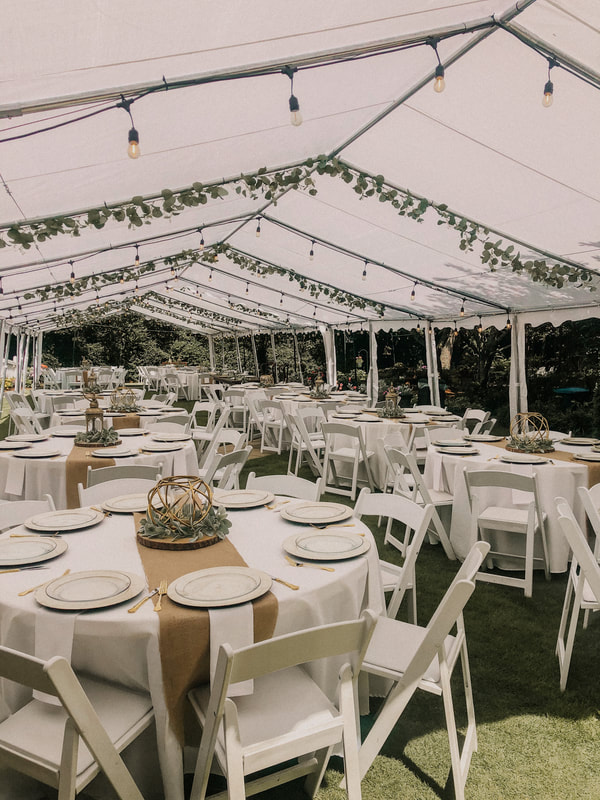 wedding reception under white tents with eucalyptus leaves