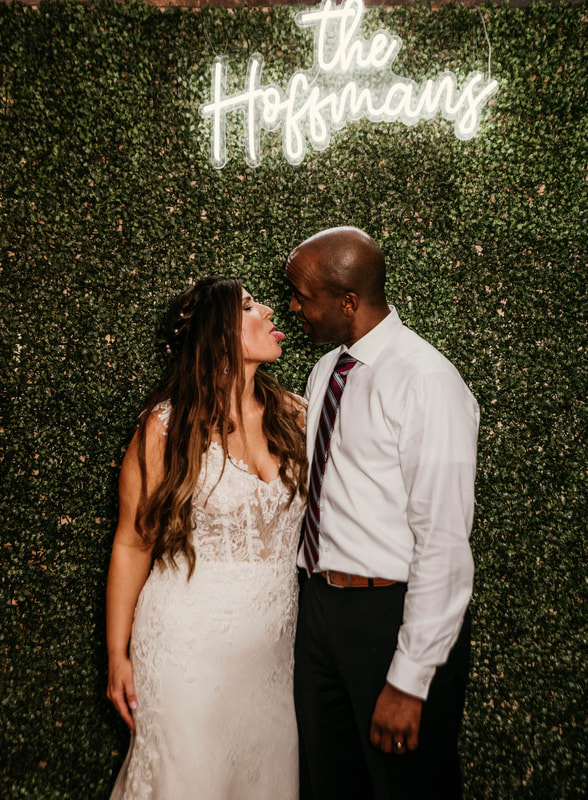 biracial couple posing in front of greenery wall with neon sign of last name