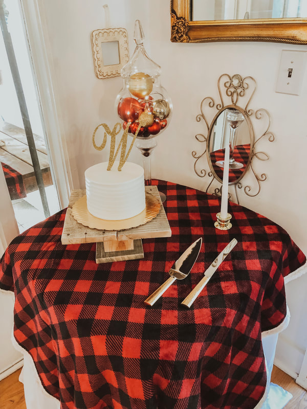 christmas themed cake table with red plaid and gold ornaments