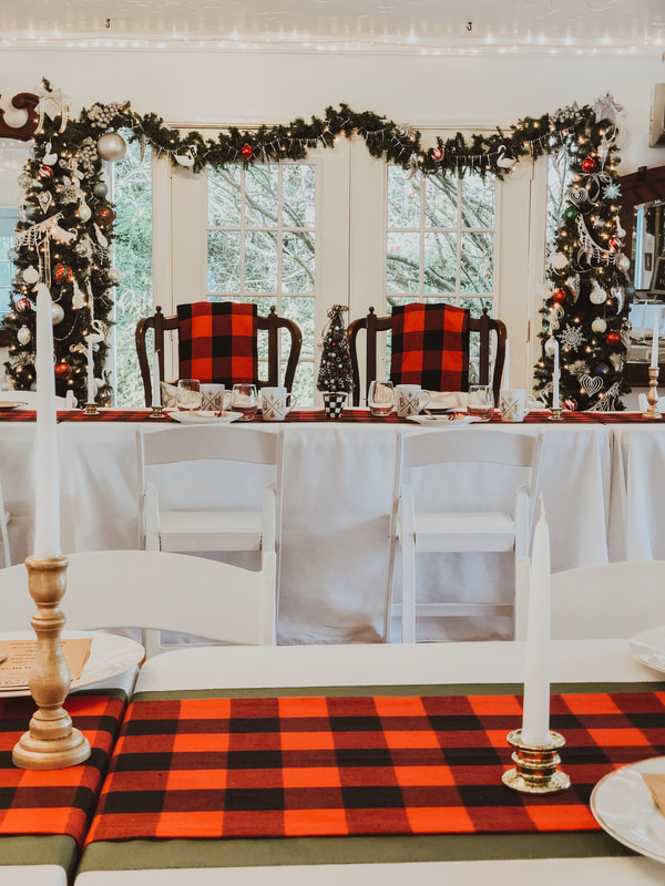Christmas inspired head table with Mr and Mrs chairs decorated with buffalo plaid blankets