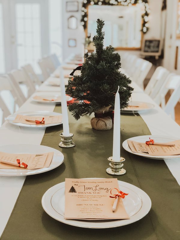 Christmas wedding tablescape with olive runner, white chargers, candlesticks, and mini Christmas trees