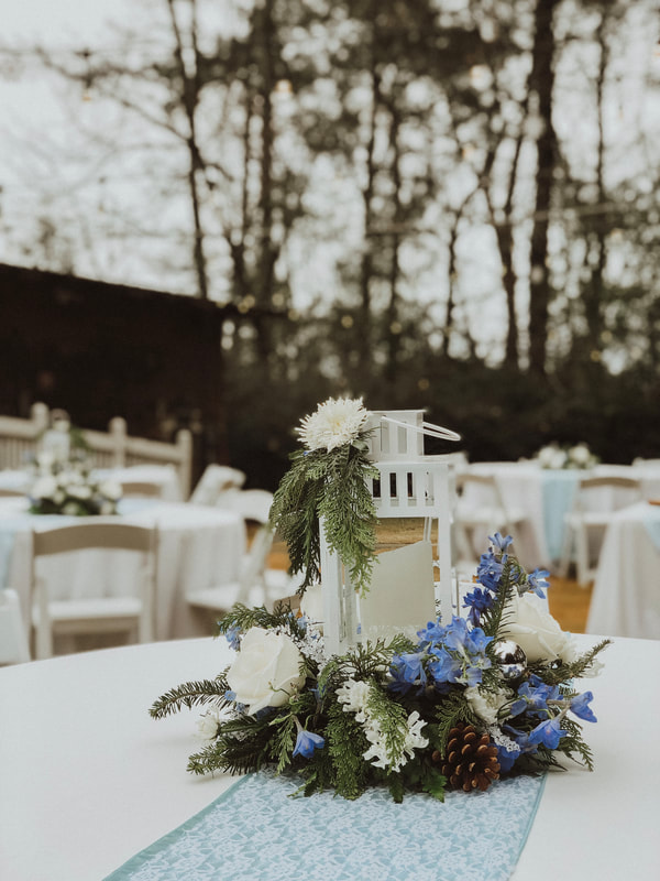 winter themed centerpieces with white lantern, evergreen leaves, and white and blue flowers