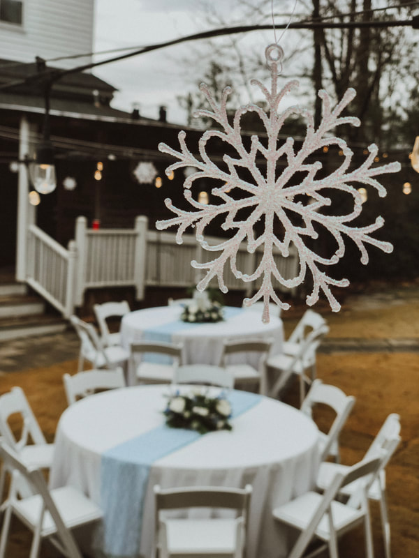 snowflake hanging from string lights overlooking reception tables
