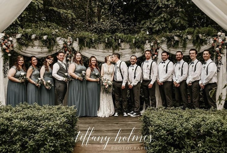 couple kissing at altar surrounded by bridal party