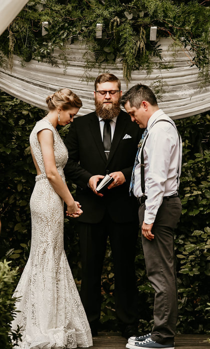 bride, groom and officiant praying by altar