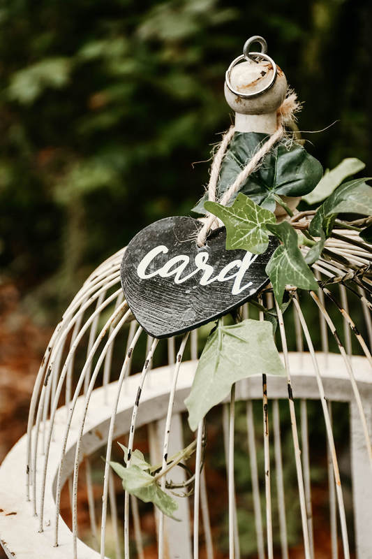 white bird cage with heart shaped calligraphy card sign